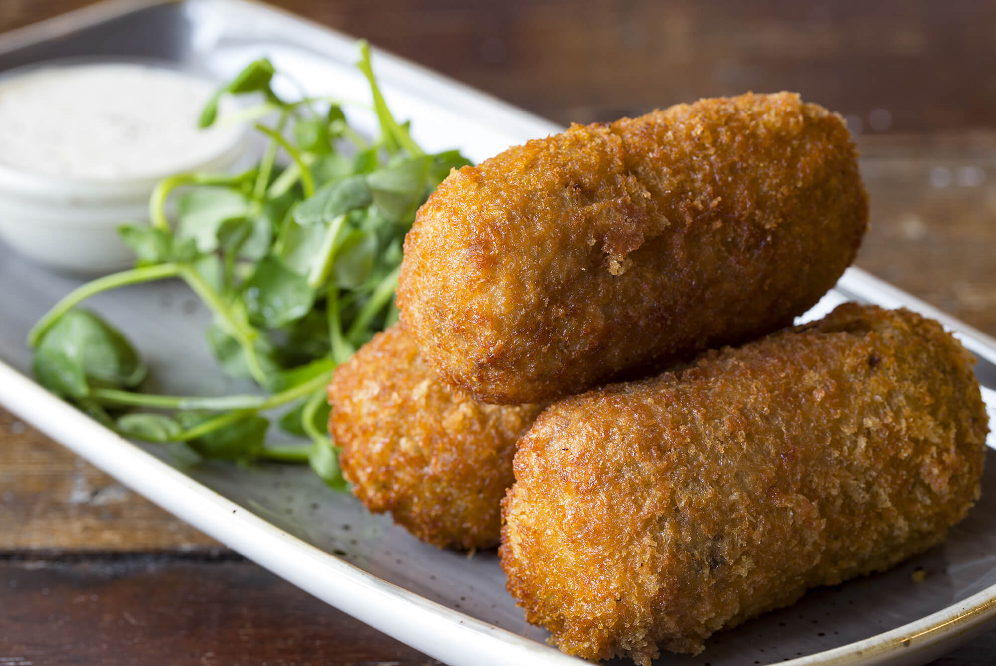 Three small breadcrumbed fried food roll containing, mashed potatoes with fish, meat or vegetables